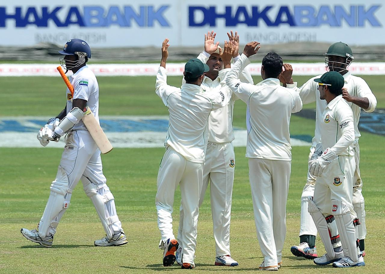 Bangladeshi cricketer's celebrates after Sri Lanka's cricket captain Angelo Mathews (L) was dismissed during the second day of their second Test match between Sri Lanka and Bangladesh at the R. Premadasa Cricket Stadium in Colombo on March 17, 2013. AFP PHOTO/ LAKRUWAN WANNIARACHCHI