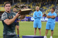 Australia's Michael Hooper holds the trophy aloft following the Rugby Championship test match between the Pumas and the Wallabies in Townsville, Australia, Saturday, Sept. 25, 2021. (AP Photo/Tertius Pickard)