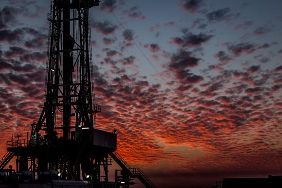 A drilling rig with a beautiful sunset in the background.