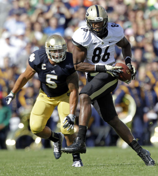 Purdue tight end Gabe Holmes (86) picks up a first down after making a catch in front of Notre Dame linebacker Manti Te'o (5) during the first half of an NCAA college football game in South Bend, Ind., Saturday, Sept. 8, 2012. (AP Photo/Michael Conroy)
