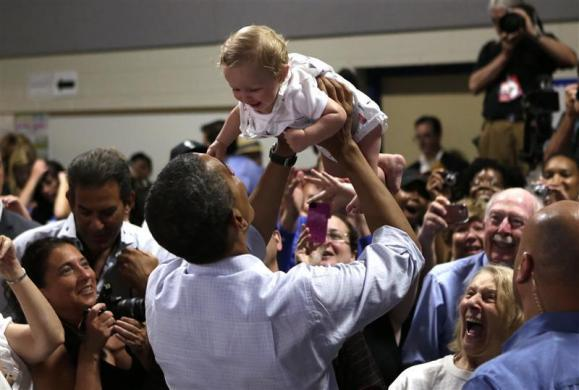 President Barack Obama holds a baby aloft during a campaign event at Dobbins Elementary School in Poland, Ohio July 6, 2012. Obama is on a two-day campaign bus tour of Ohio and Pennsylvania.