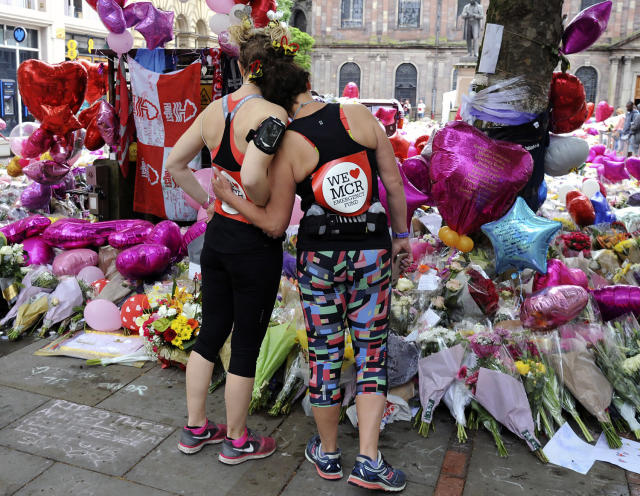 <p>Marathon runners pay respects at flower tributes in St Ann's square, before the Great Manchester Run in Manchester, England, Sunday, May 28, 2017. More than 20 people were killed in an explosion following a Ariana Grande concert at the Manchester Arena late Monday evening. (Photo: Rui Vieira/AP) </p>