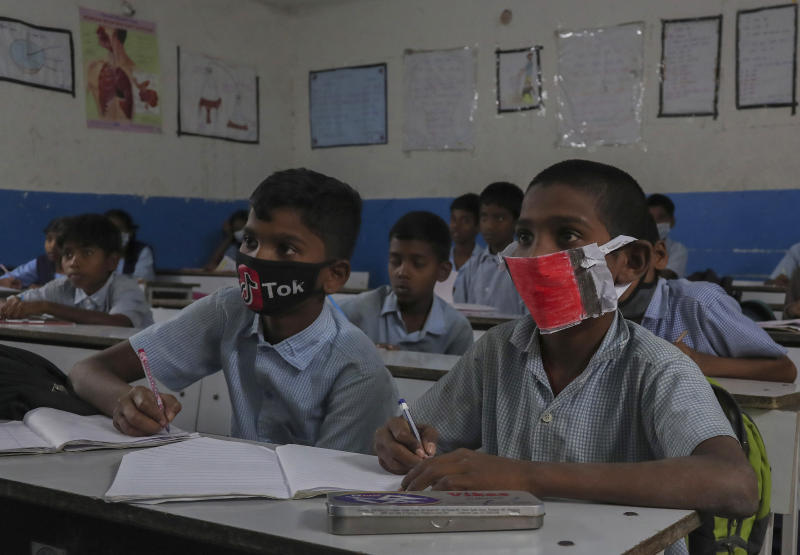 Indian students wear masks and listen to a teacher at a government school in Hyderabad, India, Wednesday, March 4, 2020. A new virus first detected in China has infected more than 90,000 people globally and caused over 3,100 deaths. The World Health Organization has named the illness COVID-19, referring to its origin late last year and the coronavirus that causes it. (AP Photo/Mahesh Kumar A.)