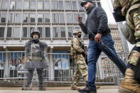 An unidentified pedestrian walks between members of the National Guard as they stand guard in front of the Philadelphia Municipal Services Building in Philadelphia, Pa., Friday, Oct. 30, 2020. (Jose F. Moreno/The Philadelphia Inquirer via AP)