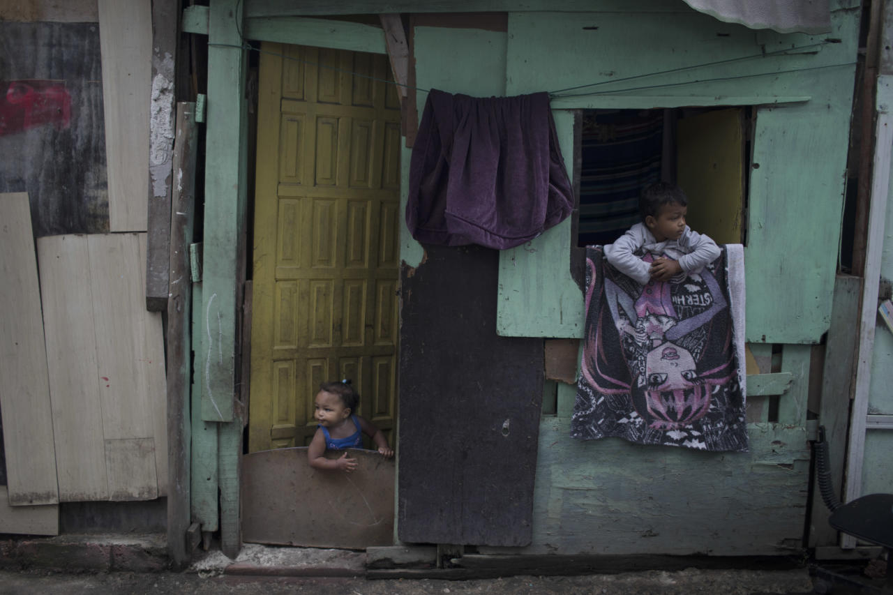 "In this June 10, 2017 photo, kids peer from their shack in the neighborhood of ""Cantinho do Ceu"" which means in Portuguese ""Heaven's corner,"" one of the poorest areas of City of God slum in Rio de Janeiro, Brazil. Many attribute soaring violence to an economic crisis that has caused Rio's unemployment rate to more than triple in recent years. (AP Photo/Leo Correa)"