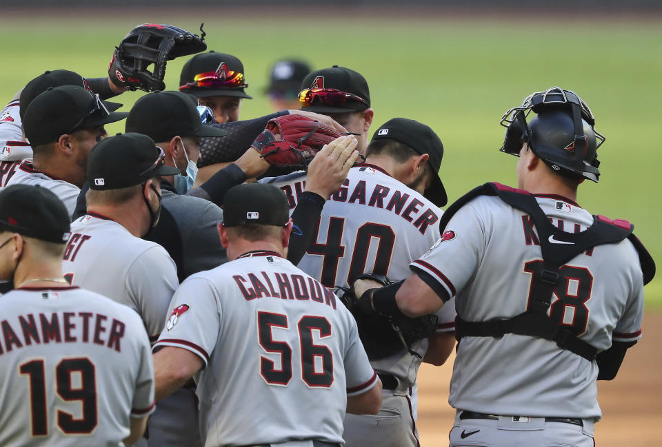 Arizona Diamondbacks starting pitcher Madison Bumgarner is swarmed by teammates as he goes the seven inning distance for a 7-0 shut out over the Atlanta Braves in the second baseball game of a double header Sunday, April 25, 2021, in Atlanta. (Curtis Compton/Atlanta Journal-Constitution via AP)