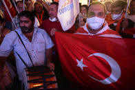 Supporters of the newly elected Turkish Cypriot leader Ersin Tatar hold a Turkish flag and celebrate winning, in the Turkish occupied area in the north part of the divided capital Nicosia, Cyprus, Sunday, Oct. 18, 2020. Ersin Tatar, a hardliner who favors even closer ties with Turkey and a tougher stance with rival Greek Cypriots in peace talks has defeated the leftist incumbent in the Turkish Cypriot leadership runoff. (AP Photo/Nedim Enginsoy)