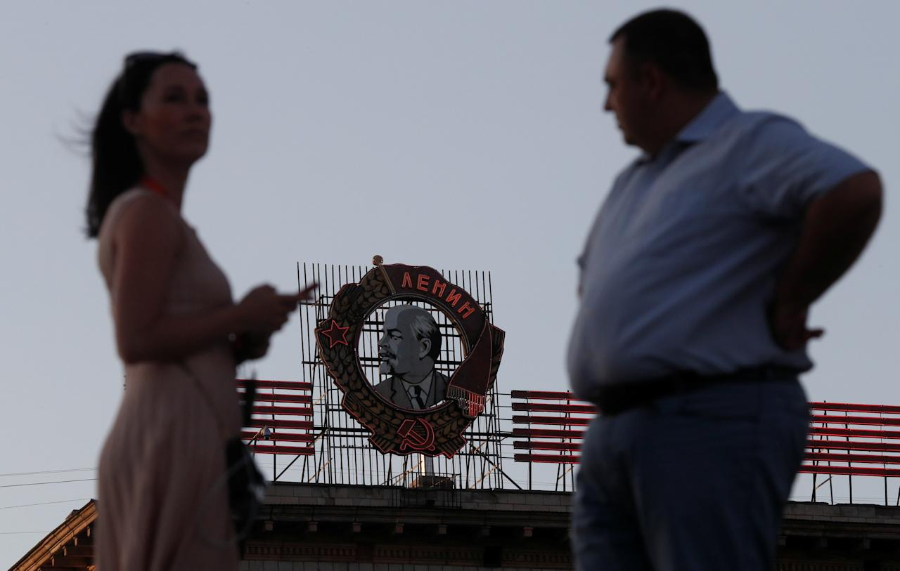 People stand in front of a residential building with the Soviet Order of Lenin seen on top, in Volgograd, Russia, August 21, 2017.  REUTERS/Maxim Shemetov