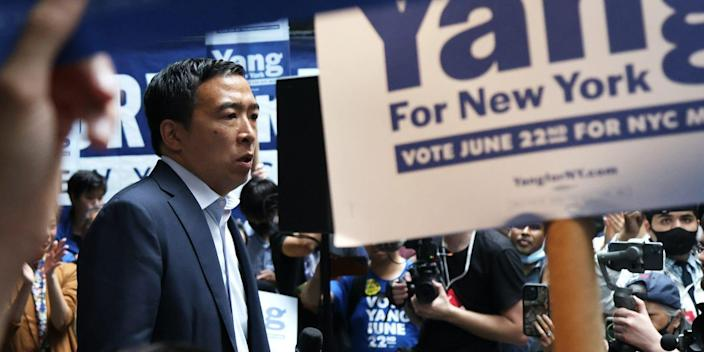 Democratic New York City mayoral candidate Andrew Yang stands at a campaign rally surrounded by supporters waving signs.