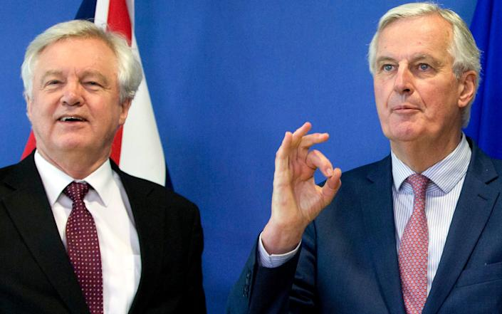 FILE - In this Monday, March 19, 2018 file photo European Union chief Brexit negotiator Michel Barnier, right, gestures as he meets with British Secretary of State for Exiting the European Union David Davis at EU headquarters in Brussels. Britain and the European Union have struck a provisional free-trade agreement that should avert New Year's chaos for cross-border commerce and bring a measure of certainty to businesses after years of Brexit turmoil. The breakthrough on Thursday, Dec. 24, 2020 came after months of tense and often testy negotiations that whittled differences down to three key issues: fair-competition rules, mechanisms for resolving future disputes and fishing rights. - Virginia Mayo/AP Photp