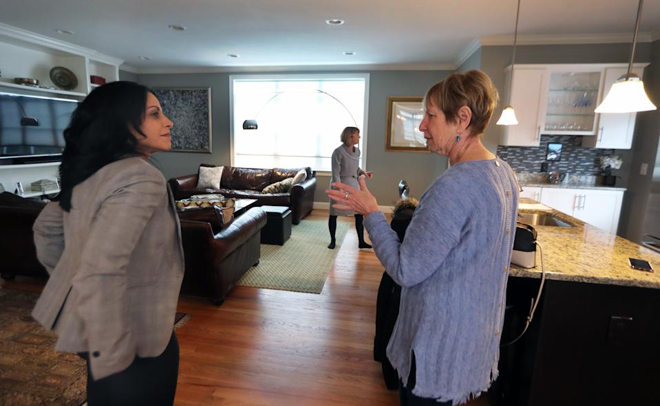 """WALTHAM, MA - FEBRUARY 24: Cynthia Pill, right, talks with broker Marie Presti, background center, and real estate agent Mary Guilloty, left, at the townhouse in Waltham, MA, that her daughter is purchasing on Feb. 24, 2019. Her daughter, Karen Fiello (not pictured), is downsizing from a 5,000-square-foot home in the Syracuse, N.Y., area. Presti, Fiellos broker, said the biggest takeaway is that when it comes to downsizing, the earlier you start the process, the better. Presti is the broker/owner of The Presti Group in Newton. She began teaching a downsizing class 10 years ago, as the first wave of baby boomers entered their 60s, and is of the ethos that Its not about downsizing, its about right-sizing."""" (Photo by Jim Davis/The Boston Globe via Getty Images)"""