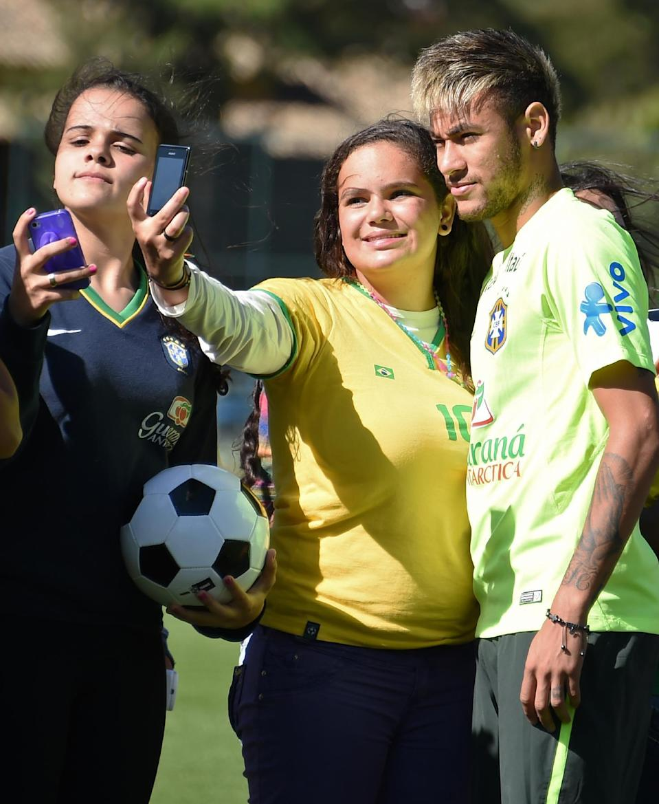 Brazil's forward Neymar poses for a selfie with a fan prior to a training session at Granja Comary training complex in Teresopolis, on June 25, 2014 as part of the FIFA 2014 World Cup in Brazil (AFP Photo/Vanderlei Almeida)