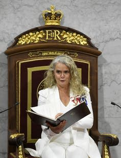 Payette, in a white suit, reads the throne speech.