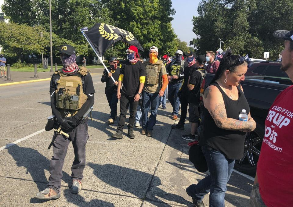 """<span class=""""caption"""">Members of the Proud Boys right-wing extremist group arrive at a pro-Donald Trump rally in Oregon in September 2020.</span> <span class=""""attribution""""><a class=""""link rapid-noclick-resp"""" href=""""https://newsroom.ap.org/detail/Election-2020-Debate-Race/1ceeb96ce01b41e79ded8fd10fbca399/photo"""" rel=""""nofollow noopener"""" target=""""_blank"""" data-ylk=""""slk:AP Photo/Andrew Selsky"""">AP Photo/Andrew Selsky</a></span>"""