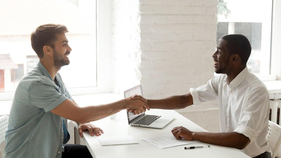 Satisfied happy african and caucasian partners shaking hands signing contract after giving bribe, smiling corrupted diverse businessmen closing deal with handshake, forming multiracial partnership.