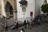 Catholic worshipers queue to enter the Omnium Sanctorum church during the Holy Week in Seville, southern Spain, Tuesday, March 30, 2021. Few Catholics in devout southern Spain would have imagined an April without the pomp and ceremony of Holy Week processions. With the coronavirus pandemic unremitting, they will miss them for a second year. (AP Photo/Laura Leon)