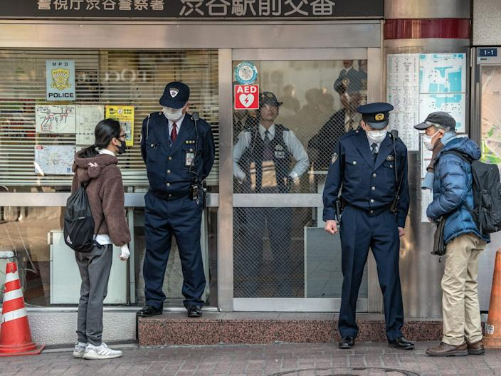 People wearing face masks ask directions from police officers who are also wearing face masks, at a police box by Shibuya crossing on February 27, 2020 in Tokyo, Japan.