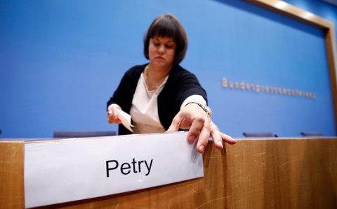 A woman removes sign with the name of Frauke Petry at the end of the Berlin news conference on Monday - Credit: Wolfgang Rattay/Reuters