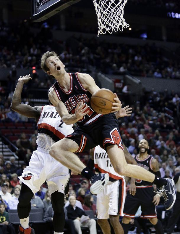 Chicago Bulls guard Mike Dunleavy, right, looks to shoot a reverse layup against Portland Trail Blazers guard Wesley Matthews during the first half of an NBA basketball game in Portland, Ore., Friday, Nov. 22, 2013. (AP Photo/Don Ryan)