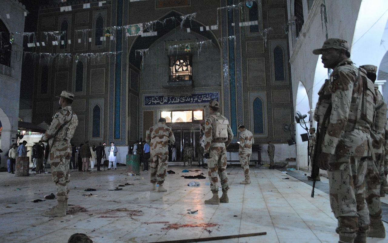 <p>Pakistani para-military soldiers stand alert after a deadly suicide attack at the shrine of famous Sufi Lal Shahbaz Qalandar in Sehwan, Pakistan, Thursday, Feb. 16, 2017. An Islamic State suicide bomber targeted worshippers at a famous shrine in southern Pakistan on Thursday, killing dozens of worshippers and left hundreds of people wounded, officials said. (AP Photo/Pervez Masih) </p>