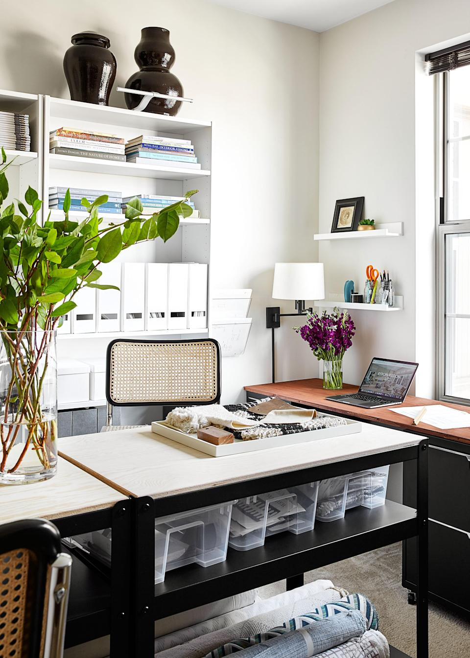 During lockdown, Risdon converted his second bedroom into an office. Installing shelving from IKEA and filing cabinets from CB2, the designer was able to stay organized during an upswing in his business. A rolling cart from IKEA offers additional storage. Swing-arm lamps from Hinson bring in a flexible light source. Like the vessels in the dining area, the vases in the office are from Roy Hamilton Studios.