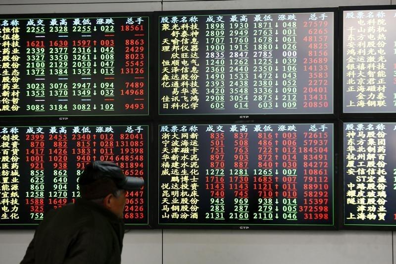An investor looks at information displayed on an electronic screen at a brokerage house in Shanghai