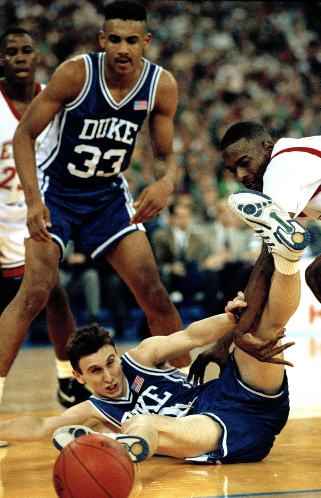 FILE - In this May 30, 1991, file photo, Duke's Bobby Hurley goes to the floor after the basketball as Stacey Augmon of UNLV, right, and teammate Grant Hill watch in the semifinal game of the NCAA Final Four in Indianapolis, March 30, 1991. A panel of Associated Press sports writers voted this game as fifth on the list of top 10 men's basketball games in the history of the NCAA Tournament.(AP Photo/Ed Reinke, File)