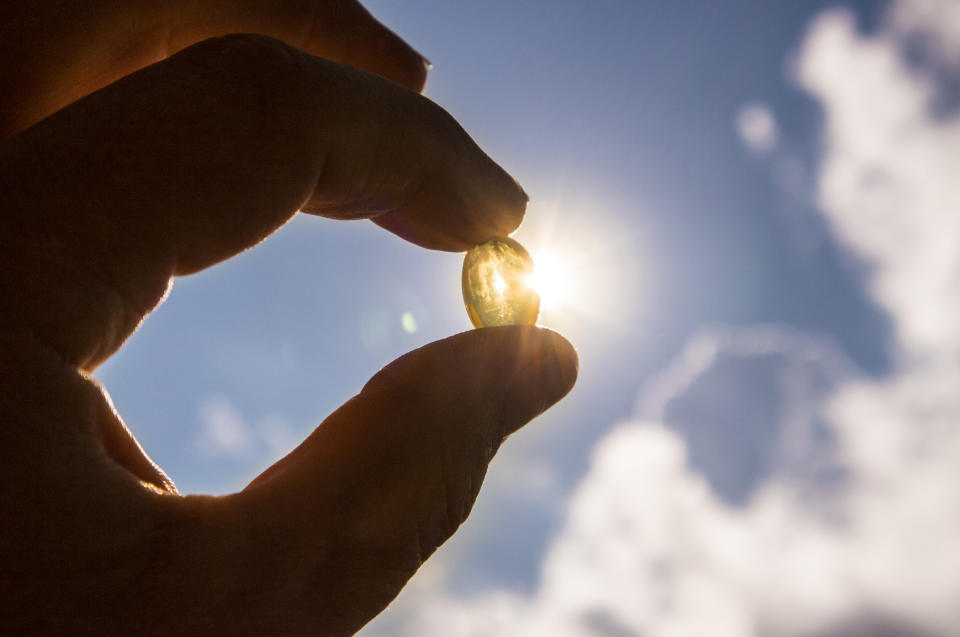 Vitamin D keeps you healthy while lack of sun. Yellow soft shell D-vitamin capsule against sun and blue sky on sunny day. Cure concept.
