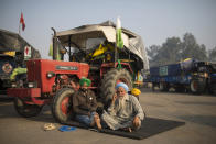 Protesting farmers, Raghuvir Singh, right, and Gurnam Singh bask in the morning sun while sitting next to their tractor parked on a highway, during a protest at the Delhi-Haryana state border, India, Tuesday, Dec. 1, 2020. Instead of cars, the normally busy highway that connects most northern Indian towns to the capital is filled with tens of thousands of protesting farmers, many wearing colorful turbans. Their convoy of trucks, trailers and tractors stretches for at least three kilometers (1.8 miles). Inside, they have hunkered down, supplied with enough food and fuel to last weeks. (AP Photo/Altaf Qadri)