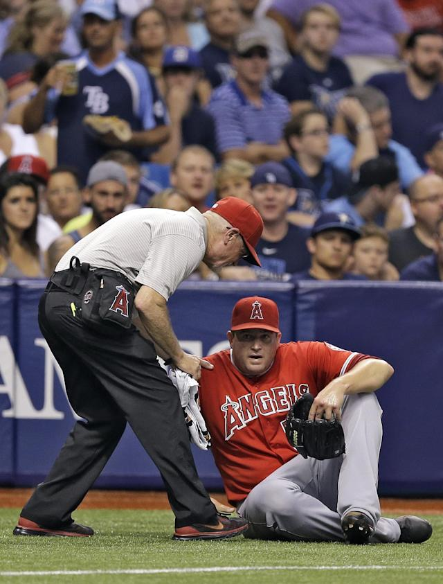 Los Angeles Angels relief pitcher Joe Thatcher is attended to by a team trainer after twisting his ankle fielding a ground ball by Tampa Bay Rays' Brandon Guyer during the fourth inning of a baseball game Saturday, Aug. 2, 2014, in St. Petersburg, Fla. Thatcher left the game. (AP Photo/Chris O'Meara)