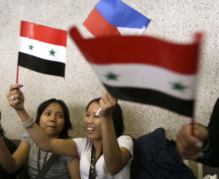 Overseas Filipino Workers, who fled the civil war in Syria, wave Syrian and Philippine flags upon arriving at the Ninoy Aquino International Airport via a chartered flight by the International Organization for Migration on Tuesday, Sept. 11, 2012, in Manila, Philippines. The nearly 300 workers, all of them young women who worked as babysitters and maids in Syria, said they were scared for their safety and sought shelter at the Philippine Embassy in Damascus until their repatriation Tuesday. (AP Photo/Bullit Marquez)