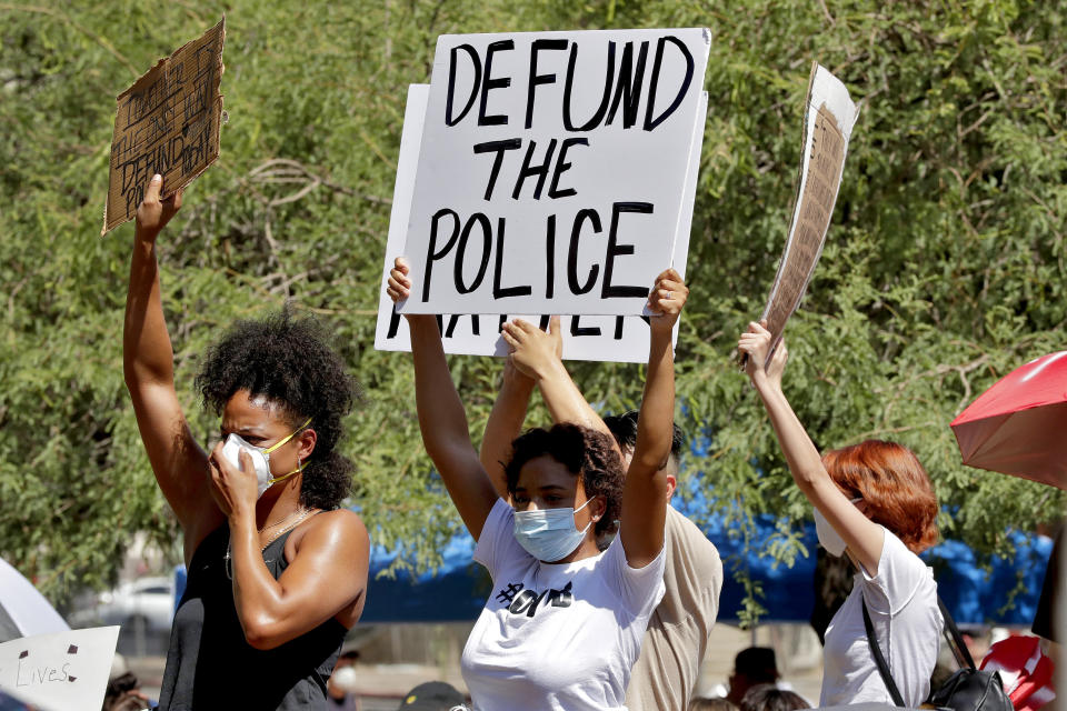 """FILE - In this June 3, 2020, file photo, protesters rally in Phoenix, demanding the Phoenix City Council defund the Phoenix Police Department. The protests sparked by Floyd's death in May thrust the defunding demand before city councils, including those in Minneapolis, Milwaukee and New York City. But defunding appears to be unpopular when voters hear it discussed in abstract, said Alex Vitale, a sociology professor at Brooklyn College in New York and author of """"The End of Policing."""" (AP Photo/Matt York, File)"""