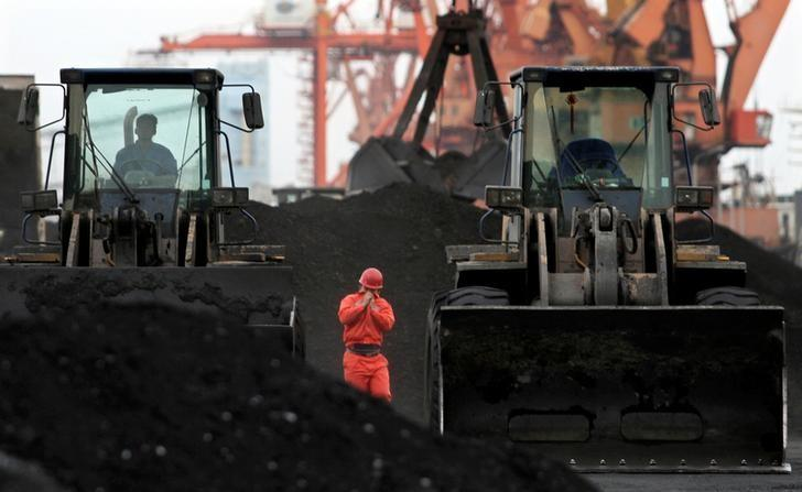 An employee walks between front-end loaders which are used to move coal imported from North Korea at Dandong port in the Chinese border city of Dandong