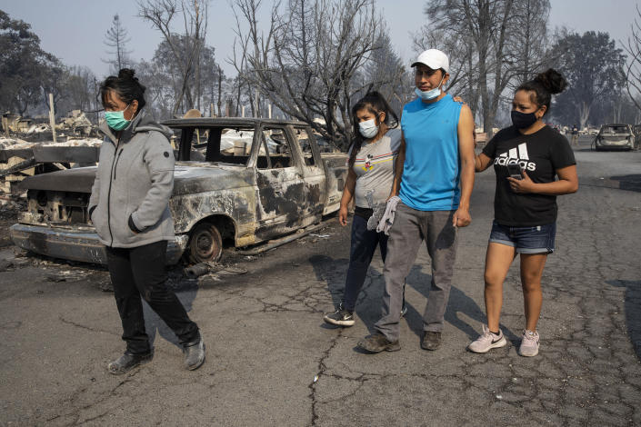 The Reyes family walks past the destruction at the Coleman Creek Estates where they lived as wild fires devastate the region on Thursday, Sept. 10, 2020, in Phoenix, Ore. The Reyes family lived in the park for 20 years. (AP Photo/Paula Bronstein)