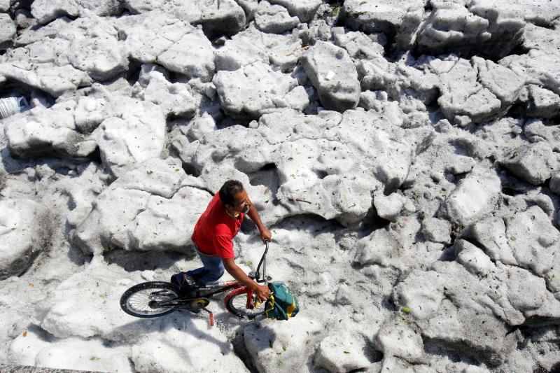 A cyclist walks on hail in Guadalajara, Mexico, on June 30. (Photo: Ulisies Ruiz/AFP/Getty Images)