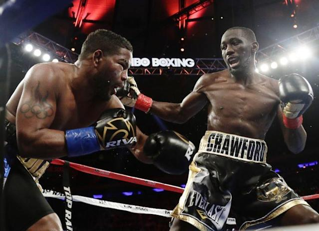 Terence Crawford (R) punishes Felix Diaz during their super lightweight title bout Saturday at Madison Square Garden. (The Associated Press)