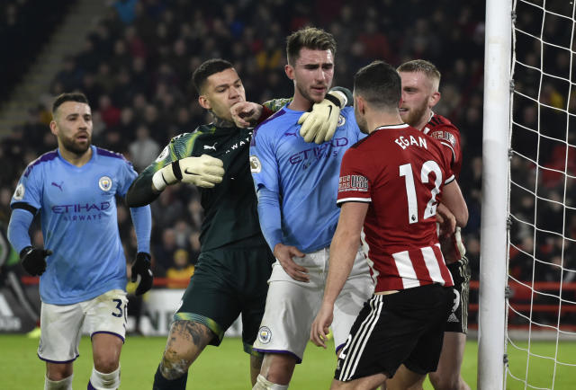 Manchester City's Aymeric Laporte, centre, scuffles with Sheffield United's John Egan, right, during the English Premier League soccer match between Sheffield United and Manchester City at Bramall Lane in Sheffield, England, Tuesday, Jan. 21, 2020. (AP Photo/Rui Vieira)