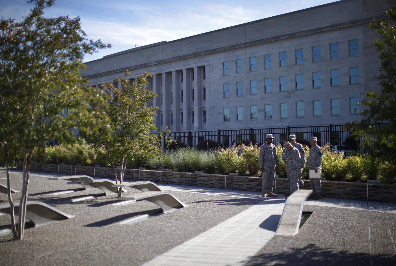 U.S. Army soldiers visit the Pentagon Memorial near Washington, August 23, 2011, near the impact site of highjacked American Airlines Flight 77 which crashed into the Pentagon (background) on September 11, 2001. The United States will commemorate the 10th anniversary of September 11, 2001 attacks next month. (REUTERS/Jason Reed)