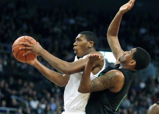 Providence's Kris Dunn, left, goes up to shoot in front of Notre Dame's Eric Atkins in the first half of an NCAA college basketball game in Providence, R.I., Saturday, Feb. 16, 2013. (AP Photo/Michael Dwyer)