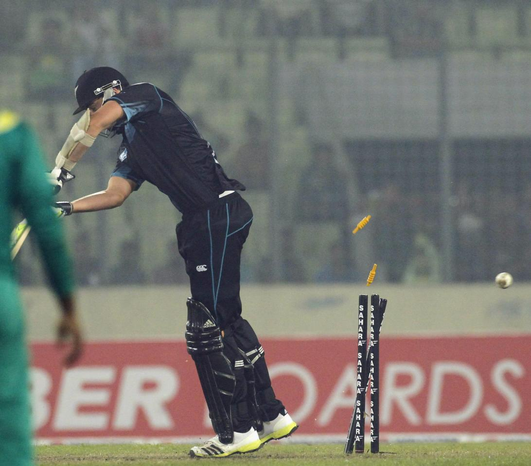 New Zealand's Kyle Mills is bowled out against Bangladesh during their second one-day international (ODI) cricket match in Dhaka October 31, 2013. REUTERS/Andrew Biraj (BANGLADESH - Tags: SPORT CRICKET)