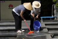 Workers wash the steps outside an entrance to the sprawling Huawei headquarters campus in Shenzhen, China, Saturday, Sept. 25, 2021. Two Canadians detained in China on spying charges were released from prison and flown out of the country on Friday, Prime Minister Justin Trudeau said, just after a top executive of Chinese communications giant Huawei Technologies reached a deal with the U.S. Justice Department over fraud charges and flew to China. (AP Photo/Ng Han Guan)