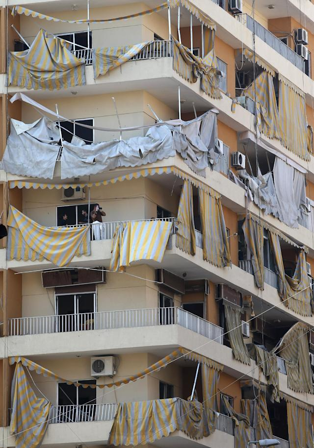A Lebanese army investigator, third floor, stands on a damaged balcony as he takes pictures near the site of a car bomb explosion, at an overwhelmingly Shiite area and stronghold of the Lebanese militant group Hezbollah, in a southern suburb of Beirut, Lebanon, Friday, Aug. 16, 2013. A powerful car bomb tore through a bustling south Beirut neighborhood that is a stronghold of Hezbollah on Thursday, killing tens of people and trapping dozens of others in an inferno of burning cars and buildings in the bloodiest attack yet on Lebanese civilians linked to Syria's civil war. (AP Photo/Hussein Malla)