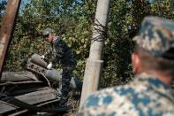 Sappers work next to a rocket case during the military conflict over the breakaway region of Nagorno-Karabakh, in Stepanakert