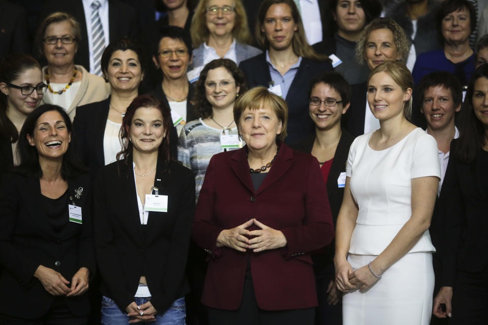 FILE - In this Wednesday, Oct. 19, 2016 file photo, German Chancellor Angela Merkel poses with women after a conference with women in leadership at the chancellery in Berlin. Millions of women admire the 67-year-old for breaking through the glass ceiling of male dominance in politics, and she's been lauded as an impressive role model for girls both at home and around the globe. (AP Photo/Markus Schreiber, File)