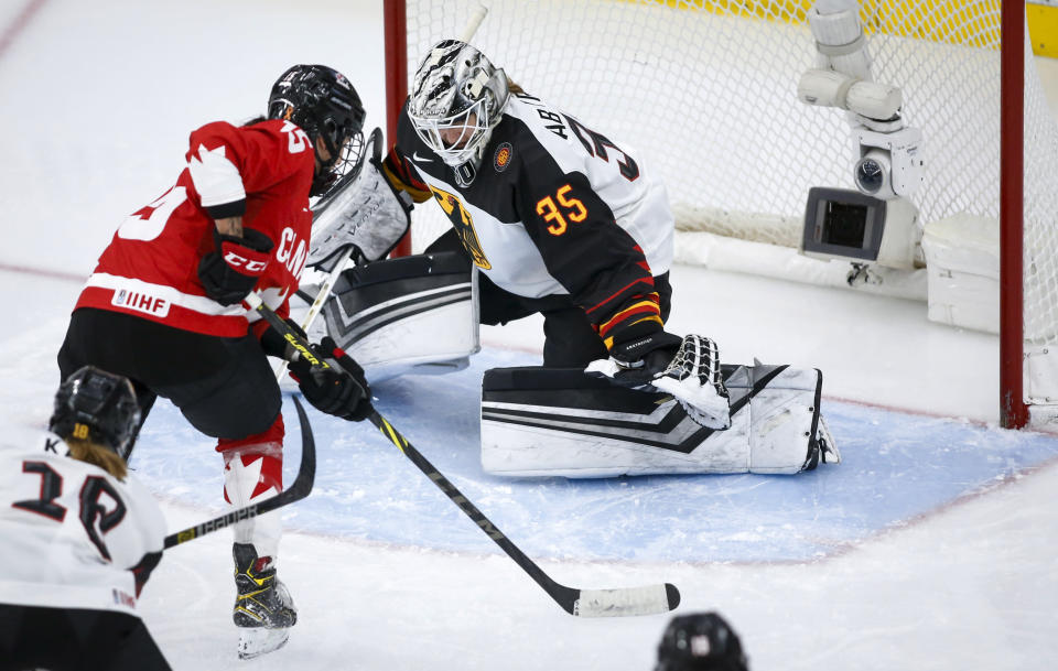 Germany goalie Sandra Abstreiter, right, blocks the net on Canada's Melodie Daoust during the third period of an IIHF women's hockey championships quarterfinal in Calgary, Alberta, Saturday, Aug. 28, 2021. (Jeff McIntosh/The Canadian Press via AP)