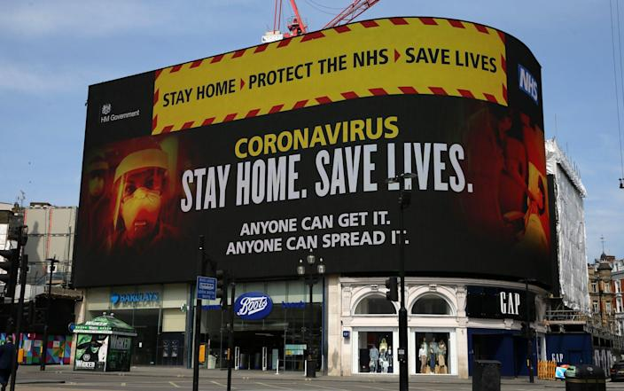 "A NHS signage about coronavirus advice people to ""Stay home. Save lives"" is displayed on the advertising boards at Piccadilly Circus in London - The story behind 'Stay Home, Protect the NHS, Save Lives' - GETTY IMAGES"