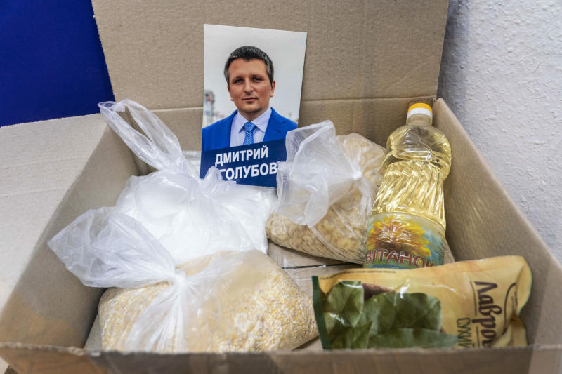 """In this photo taken on Friday, July 12, 2019, a portrait of a candidate, packets of grains and food are displayed in an exhibition at the National History Museum, in Kiev, Ukraine. A Darth Vader costume, playground equipment, pastries and boxes of food all are part of an exhibit at Ukraine's National History Museum displaying the colorful behavior and sometime-questionable practices that characterize the country's elections. The exhibition, called """"The Museum of Election Trash"""" was put together ahead of the  snap parliamentary elections on Sunday, July 21, 2019. (AP Photo/Evgeniy Maloletka)"""