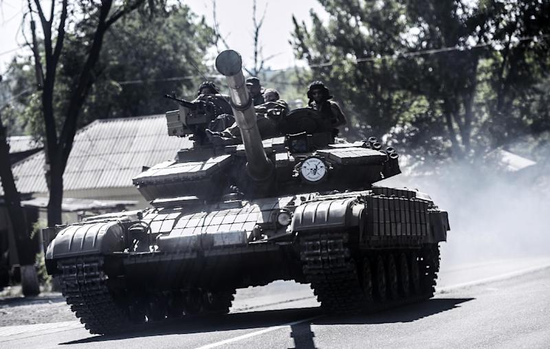 Pro-Russian militants sit on a tank on July 27, 2014 in Donetsk, eastern Ukraine, as they drive to the front line south of the city (AFP Photo/Bulent Kilic)