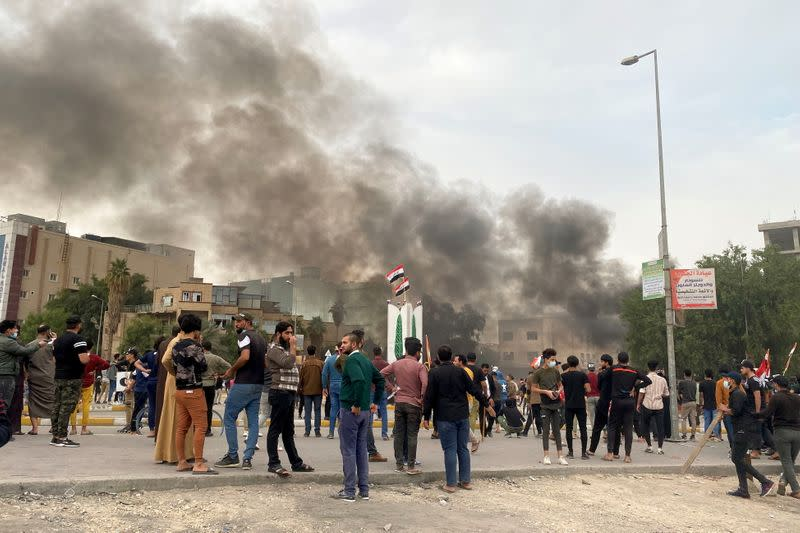 Smoke rises during clashes between anti-government protesters and supporters of Iraqi Shi'ite cleric Moqtada al-Sadr in Nassiriya