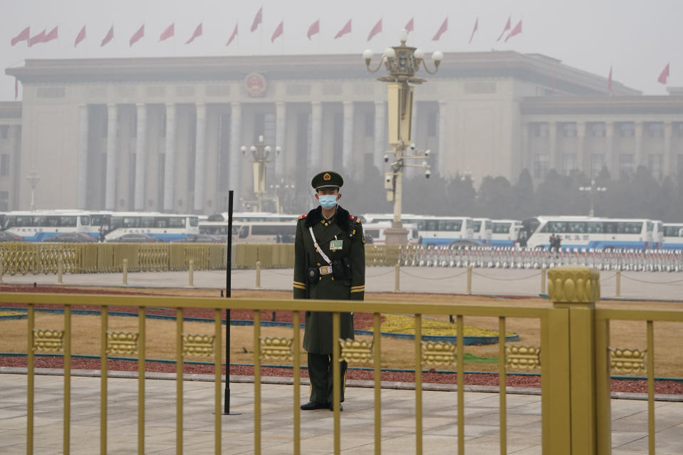 """A Chinese paramilitary policeman stands watch near the Great Hall of the People where the annual National People's Congress is held in Beijing on Friday, March 5, 2021. The ruling Communist Party is aiming for economic growth """"over 6%"""" as it rebounds from the coronavirus pandemic, Premier Li Keqiang said in a speech at China's ceremonial legislature Friday. (AP Photo/Ng Han Guan)"""